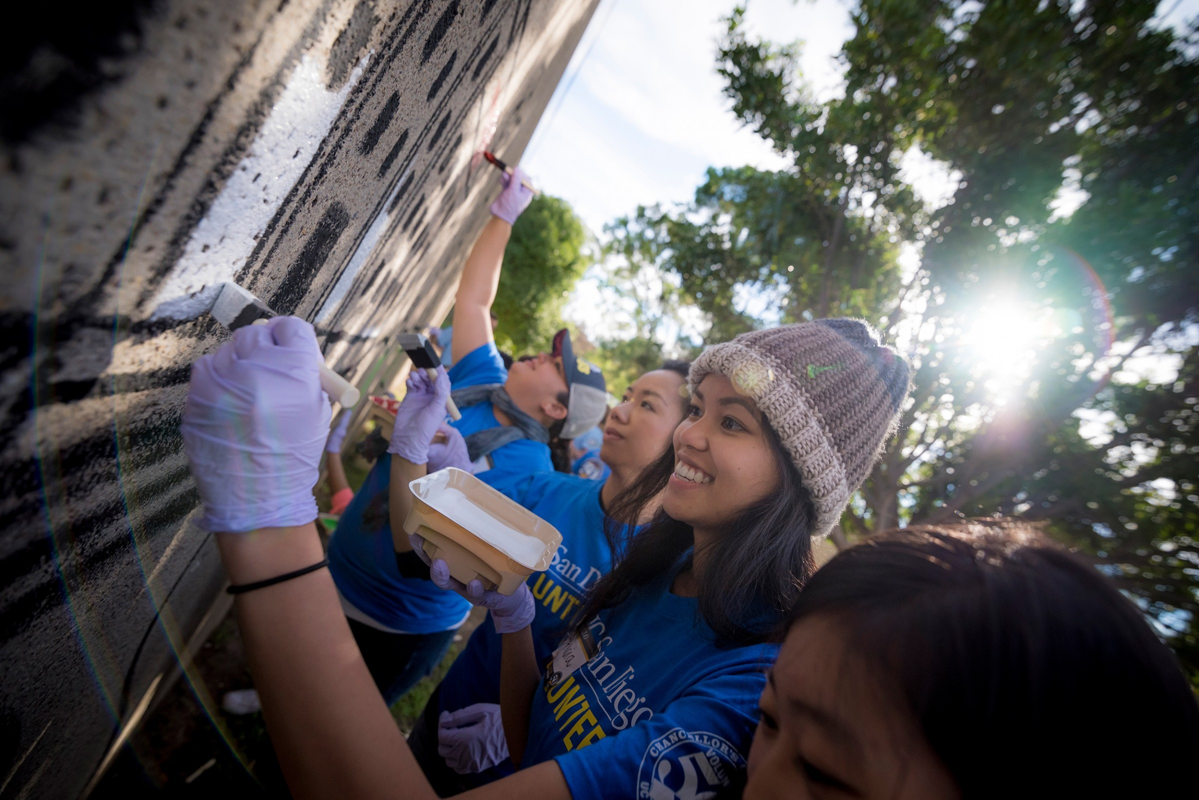 student volunteers painting a wall