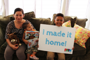 """Family of 3 holding a """"I made it home"""" sign"""