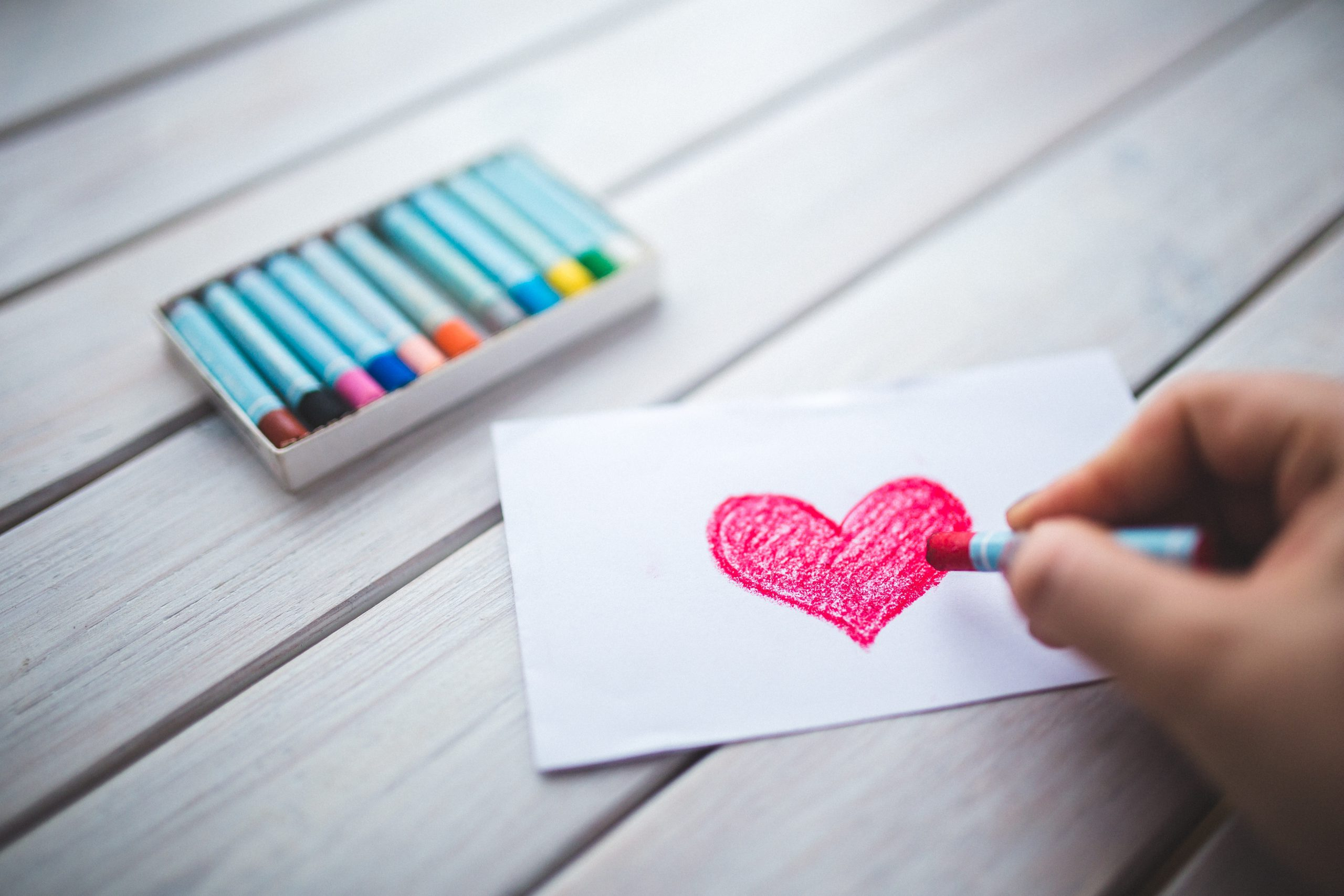 someone's hand drawing a heart on paper