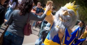 Mascot high-fiving a participant at the event.